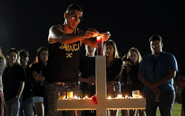 Joey Kandil, 18, a recent graduate of Marjory Stoneman Douglas High School, places a ring around a candle on one of seventeen crosses, after a candlelight vigil for the victims of the Wednesday shooting at the school, in Parkland, Florida., February 15, 2018. (AP Photo/Gerald Herbert)