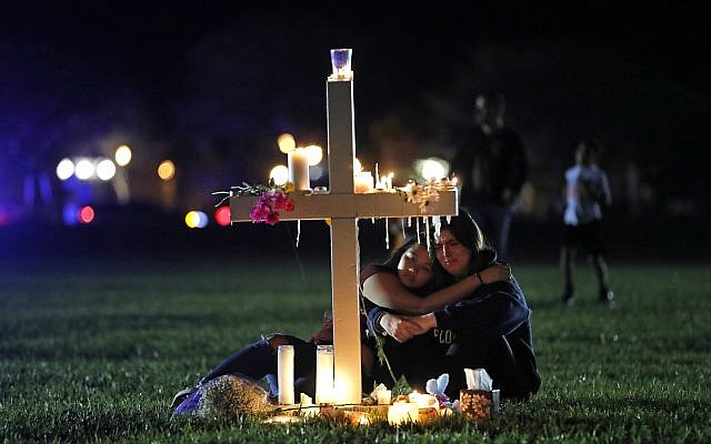 Two people comfort each other as they sit and mourn at one of seventeen crosses, after a candlelight vigil for the victims of the Wednesday shooting at Marjory Stoneman Douglas High School, in Parkland, Florida, February 15, 2018. (AP Photo/Gerald Herbert)