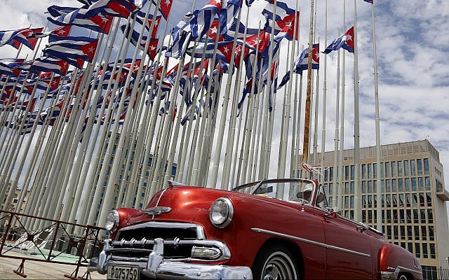 A classic American convertible car passes beside the United States embassy as Cuban flags fly beside in Havana, Cuba. (AP Photo/Desmond Boylan, File)