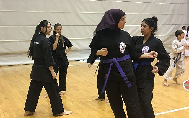 Two young students practicing martial arts techniques during the Budo for Peace Seminar, February 13, 2018 (Urvashi Verma/Times of Israel)