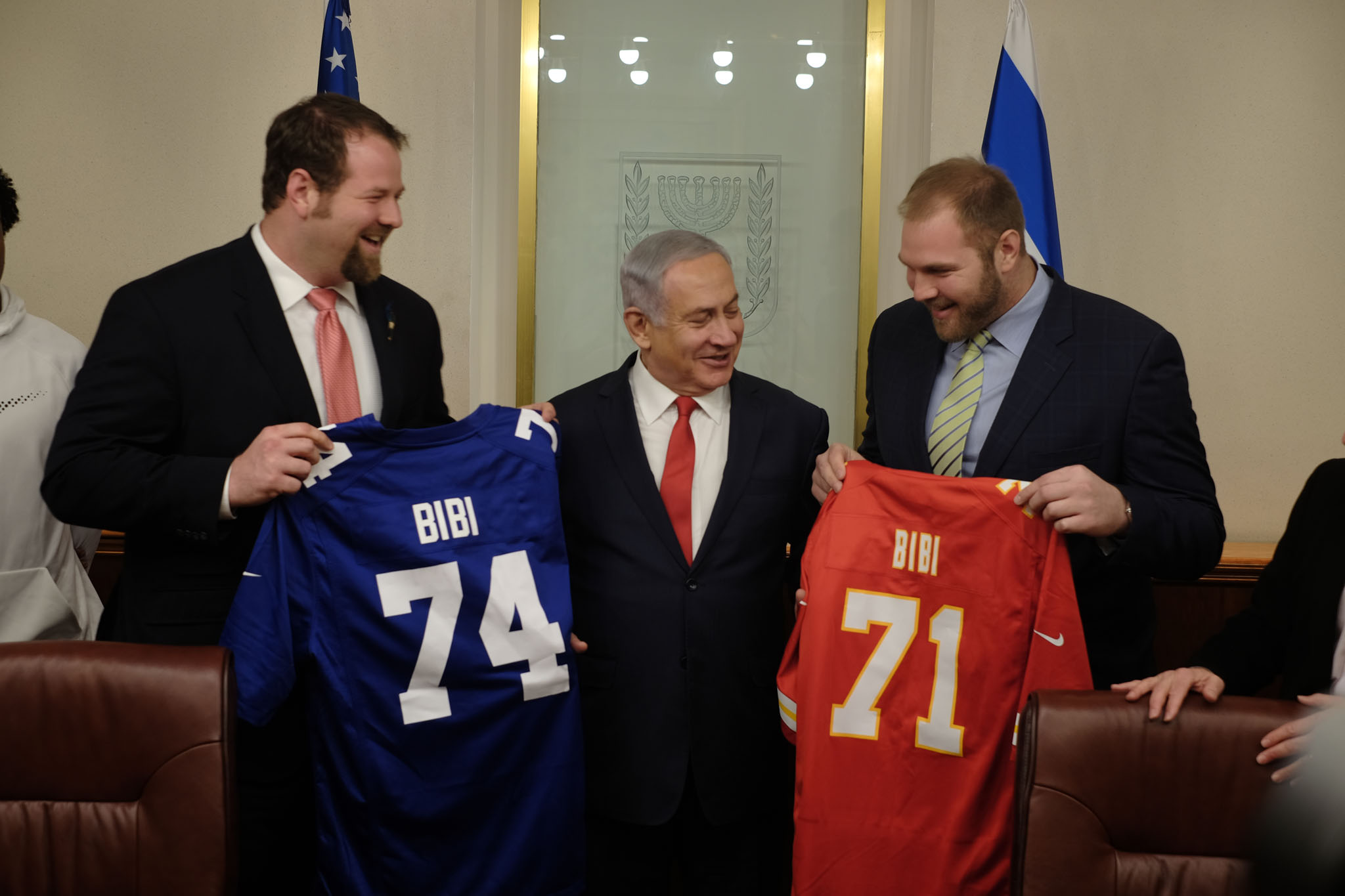 Jewish NFL football players and brothers Geoff (l) and Mitchell (r) Schwartz present Prime Minister Benjamin Netanyahu with football jerseys that have his nickname on them, in his Jerusalem office, on February 19, 2018. (Judah Ari Gross/Times of Israel)