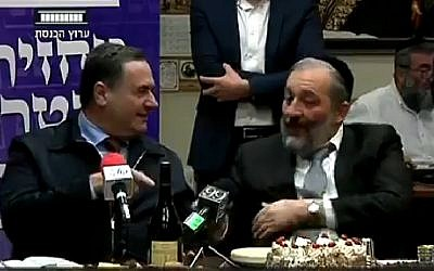 Transport Minister Israel Katz (Likud, left) and Interior Minister Aryeh Deri (Shas) joke about Prime Minister Benjamin Netanyahu's incredible luck, on February 26, 2018. (Screen capture: Knesset Channel)
