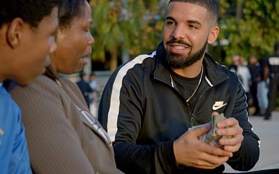 Canadian Jewish rapper Drake (r) gives away a stack of cash to a needy mother and son in his music video 'God's Plan,' released February 16, 2018. (Screen capture: YouTube)