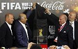 Palestinian businessman Zahi Khouri (2nd R) unveils the FIFA World Cup trophy as Palestinian Football Association chairman Jibril Rajoub (2nd L) applauds during the first stop of the FIFA World Cup Trophy Tour in the West Bank city of Ramallah. November 10, 2013. ( Issam RImawi/FLASH90)