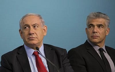 Prime Minister Benjamin Netanyahu (L) and then finance minister Yair Lapid attend a signing ceremony at the Prime Minister's Office in Jerusalem on September 23, 2014.(Noam Revkin Fenton/Flash90)