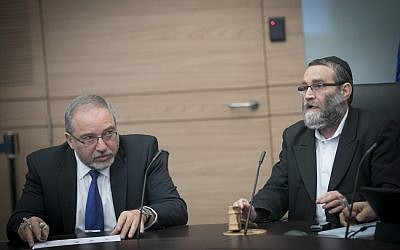 Defense Minister Avigdor Liberman (L) and United Torah Judaism MK Moshe Gafni at a Knesset Finance Committee meeting on December 6, 2016. (Yonatan Sindel/Flash90)