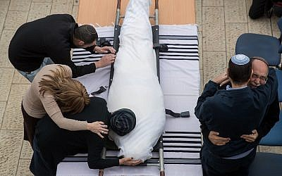 Friends and family of Rabbi Itamar Ben-Gal mourn beside his body during his funeral in Har Bracha on February 6, 2018. Ben-Gal was fatally stabbed by a Palestinian terrorist at the entrance to Ariel, in the West Bank, a day earlier. (Yonatan Sindel/Flash90)