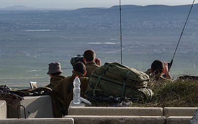 Israeli soldiers survey the border with Syria from a military post in the Golan Heights, following a series of aerial clashes with Syrian and Iranian forces in Syria, on February 10, 2018. (Flash90)