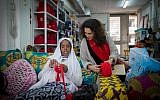 Dr Diddy Mymin Kahn, co-founder and director of the Kuchinate collective, looks on as Selam crochets a basket at the Kuchinate workshop in Tel Aviv, on January 3, 2018. (Miriam Alster/Flash90)