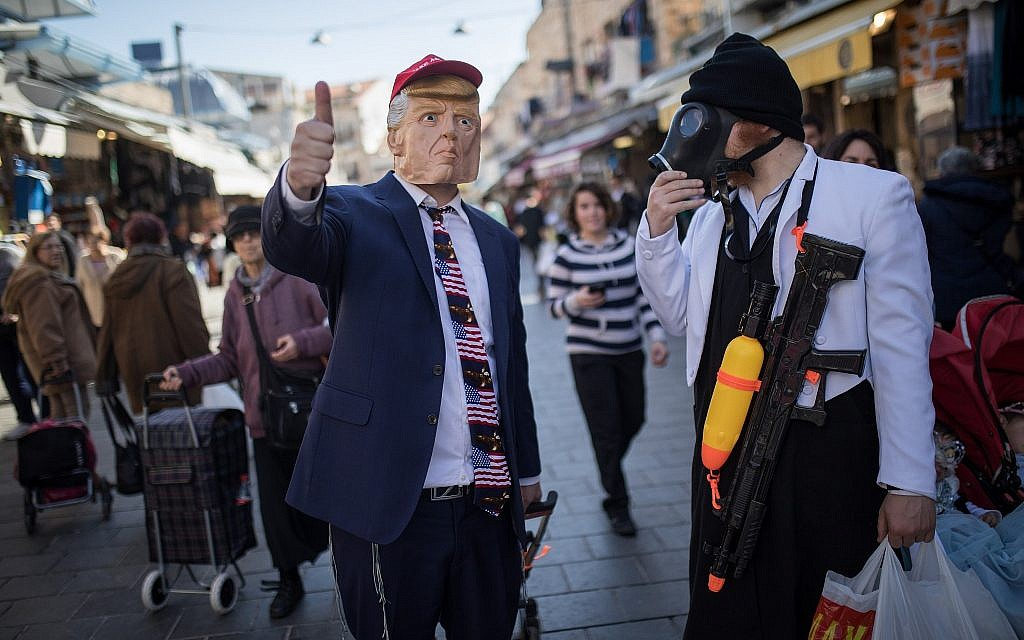 People dressed up in costumes for the Jewish holiday of Purim shop at Jerusalem's Mahane Yehuda market on February 28, 2018. (Hadas Parush/Flash90)