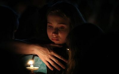 A young girl clutches a friend during candlelight vigil for victims of the mass shooting at Marjory Stoneman Douglas High School yesterday, at Pine Trail Park, in Parkland, Fla., Feb. 15, 2018. (Mark Wilson/Getty Images, via JTA)