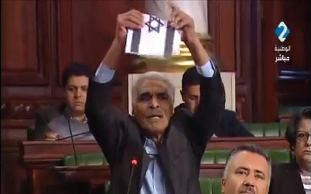 Tunisian lawmaker Ammar Amroussia tears up an Israeli flag during a session of parliament on February 13, 2018. (Screen capture: Twitter)