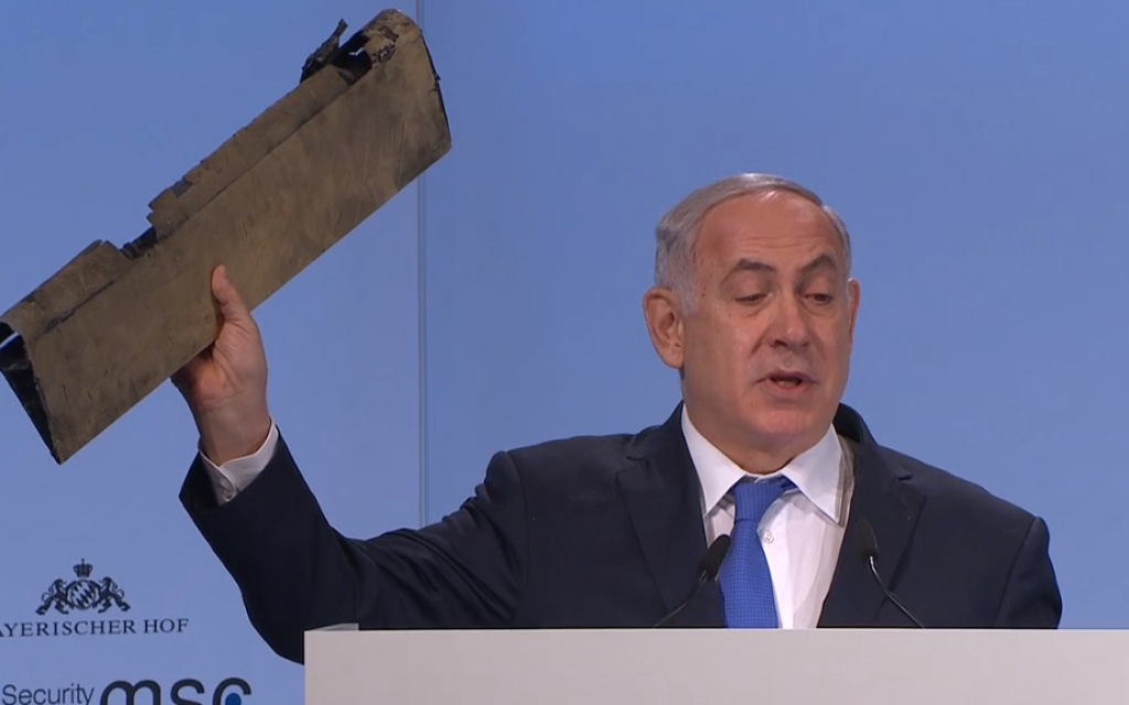 Prime Minister Benjamin Netanyahu waves part of an Iranian drone downed in Israeli airspace on February 10, 2018, during a speech on the third day of the 54th Munich Security Conference (MSC) held at the Bayerischer Hof hotel, in Munich, southern Germany, on February 18, 2018. (Screen capture)