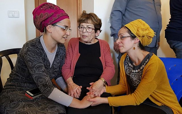 Yael Shevach (L), the wife of Raziel Shevach who was gunned-down in a  January 9 terror attack near the Havat Gilad outpost consoles Miriam Ben-Gal, the wife of Itamar Ben-Gal, who was stabbed to death in a February 5 terror attack. Photo taken at Ben-Gal home on February 6, 2018. In the middle is Miriam's grandmother Esther. (Courtesy)