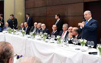 Prime Minister Benjamin Netanyahu, right, addresses dozens of senior business leaders, encouraging them to invest in Israel, ahead of the Munich Security Conference, February 16, 2018. (Amos Ben Gershom/GPO)