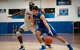 Gabriel Leiter of Yeshiva University drives on a Purchase College defender in the Skyline Conference championship game, February 25, 2018. (Courtesy of Yeshiva University via JTA)
