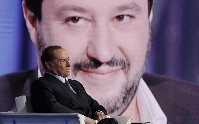 Former Italian Prime Minister and Forza Italia (Go Italy) party leader, Silvio Berlusconi, is backdropped by The League party leader Matteo Salvini during the recording of the Italian state television RAI, Porta a Porta (Door To Door) talk show in Rome, January 11, 2018. (AP Photo/Andrew Medichini)