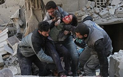 Syrians rescue a child following a reported regime air strike in the rebel-held town of Hamouria, in the besieged Eastern Ghouta region on the outskirts of the capital Damascus on February 21, 2018.  (AFP PHOTO / ABDULMONAM EASSA)