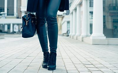 Closeup of female legs in black pants and boots. Woman walking in the city. (iPhoto)