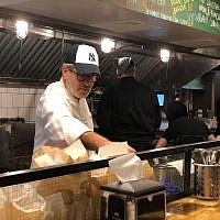 Israeli chef Eyal Shani prepares a pita in the newly-opened New York branch of his Miznon restaurant chain. (Danielle Ziri/Times of Israel)