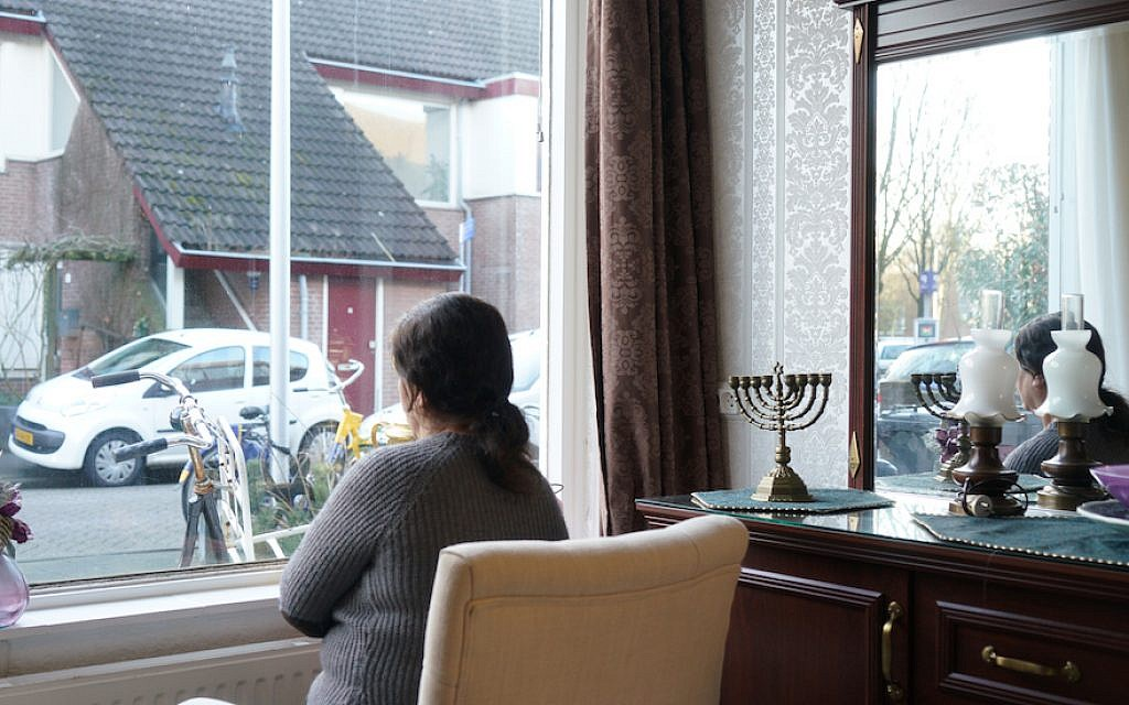 Sipora, a Jewish refugee from Iran, looking out the window of her daughter's Netherlands home, Feb. 15, 2018. (Cnaan Liphshiz)