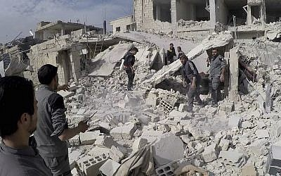 This photo provided by the Syrian Civil Defense White Helmets and authenticated, based on its contents and other AP reporting, shows civil defense workers and civilians inspecting a damaged building after airstrikes hit a rebel-held suburb near Damascus, Syria, on February 8, 2018. (Syrian Civil Defense White Helmets via AP)