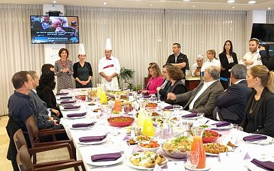 Knesset lawmakers tuck into vegan alternatives to their meat and dairy favorites in support of annual Animal Rights Day. Tamar Zandberg (Meretz), who hosted the feast, stands at the end of the table next to the chefs, February 6, 2018. (Anonymous for Animal Rights).
