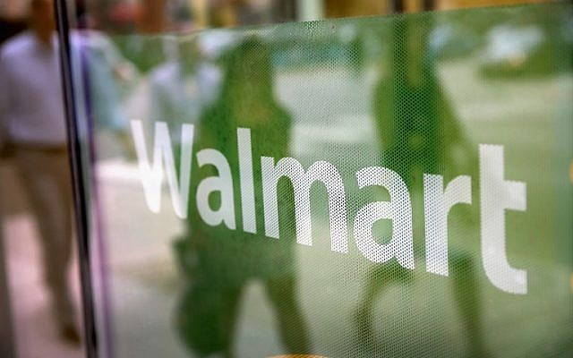 The Walmart logo displayed in the window of a Walmart Neighborhood Market store in Chicago, Illinois, August 15, 2013. (AFP Photo/Getty Images North America/Scott Olson)