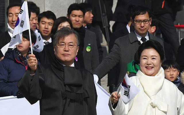 South Korea's President Moon Jae-in and his wife Kim Jung-sook wave national flags during a ceremony marking the 99th Independence Movement Day against the 1910-1945 Japanese colonial rule in Seoul on March 1, 2018. (AFP PHOTO / Jung Yeon-je)