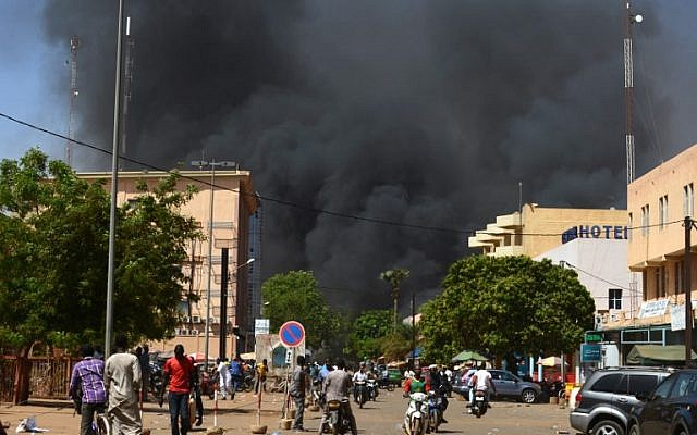 People watch as black smoke rises as the capital of Burkina Faso came under multiple attacks on March 2, 2018, targeting the French embassy, the French cultural center and the country's military headquarters. (AFP PHOTO / Ahmed OUOBA)