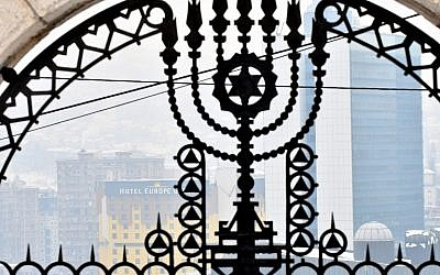 This photograph taken on February 23, 2018, shows a gate at the entrance of The Jewish Cemetery with the background of the city center of Sarajevo. (AFP PHOTO / ELVIS BARUKCIC)