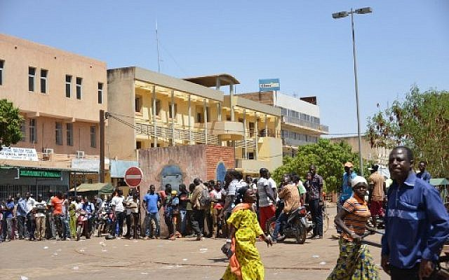 Bystanders watch the scene outside the headquarters of the country's defense forces in Ouagadougou on March 2, 2018 after dozens of people were killed in twin attacks on the French embassy and the country's military. (AFP PHOTO / Ahmed OUOBA)