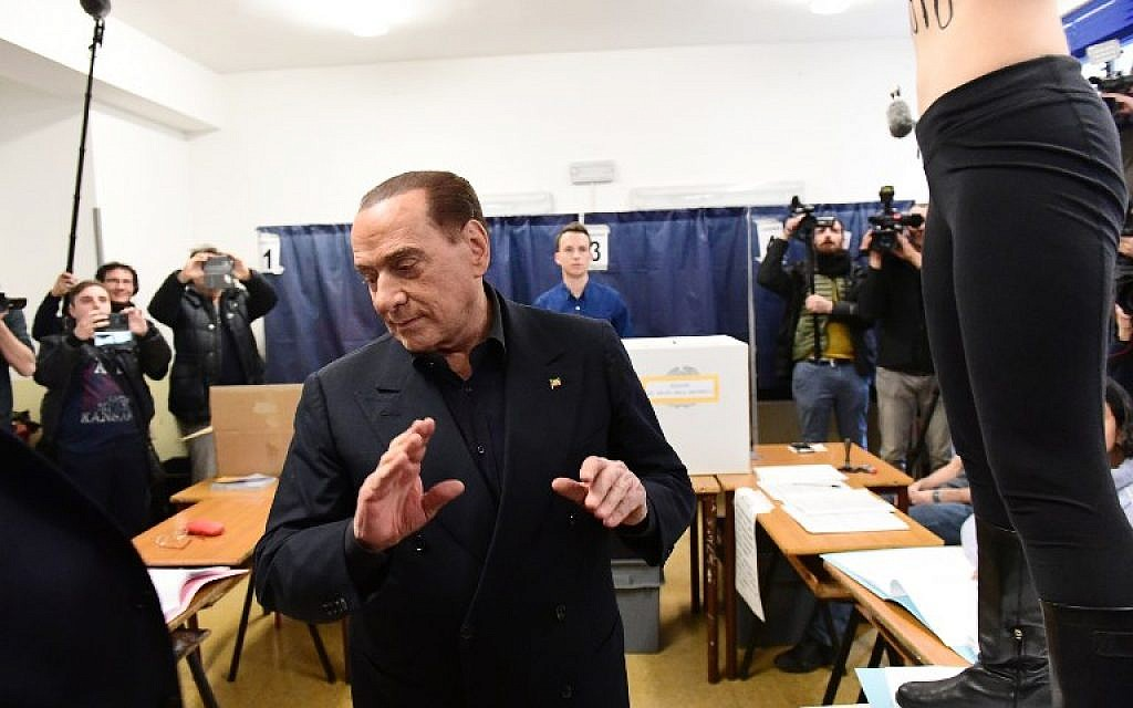 A topless demonstrator jumps on a table in front of Silvio Berlusconi, leader of the Forza Italia party, as he casts hit vote in Milan on March 4, 2018. (AFP Photo/Miguel Medina)