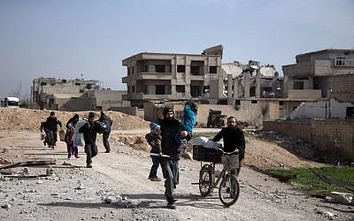 Syrians flee their homes with their belongings in the town of Beit Sawa in Syria's besieged Eastern Ghouta region on March 4, 2018, following reported regime air strikes. (AFP Photo/Abdulmonam Eassa)