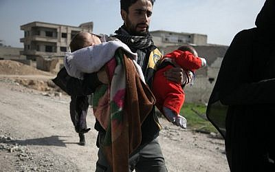 A Syrian civil defense volunteer carries children, as he helps them try to flee their homes in the town of Hamouria in Syria's besieged eastern Ghouta region on March 4, 2018, following reported airstrikes. (AFP PHOTO / ABDULMONAM EASSA)