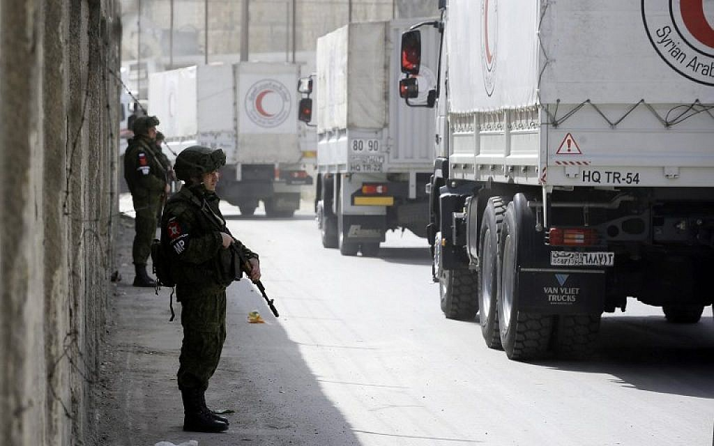 Russian soldiers stand guard as Syrian Arab Reb Crescent trucks carrying aid drive through the al-Wafideen checkpoint on the outskirts of Damascus towards the rebel-held Eastern Ghouta region on March 5, 2018. (AFP Photo/Louai Beshara)