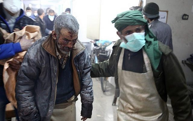 A wounded Syrian man is brought into a clinic in Syria's Eastern Ghouta