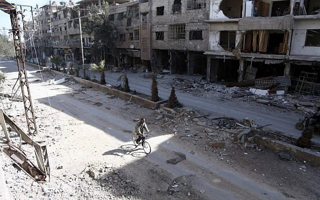 A Syrian man rides his bike amidst the destruction in the rebel-held town of Hamouria in the besieged Eastern Ghouta region on the outskirts of the capital Damascus