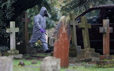 A member of the emergency services wearing a protective suit works at the London Road Cemetery in Salisbury, southern England, on March 10, 2018, where the wife and son of former Russian spy Sergei Skripal are buried. (AFP PHOTO / Daniel LEAL-OLIVAS)