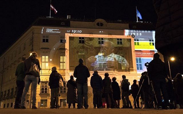 """People watch 'Zeituhr 1938', a projection on the facade of the Austrian Chancellery that retraces the dark moments leading to the Nazi takeover by Adolf Hitler in 1938, one day ahead of the 80th anniversary of Austria's annexation (""""Anschluss""""), on March 11, 2018 in Vienna, Austria. (AFP PHOTO / JOE KLAMAR)"""
