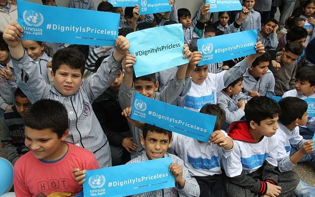 Palestinian refugees hold placards at a school belonging to the United Nations Relief and Works Agency for Palestinian Refugees (UNRWA) in the town of Sebline east of the southern Lebanese port of Saida, on March 12, 2018, during a protest against US aid cuts to the organization. (AFP PHOTO / Mahmoud ZAYYAT)
