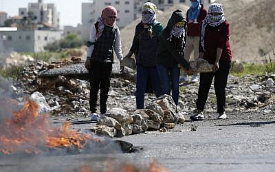Palestinian demonstrators carry stones during clashes with Israeli soldiers on March 12, 2018 in the West Bank town of Birzeit, near Ramallah. (AFP/ABBAS MOMANI)