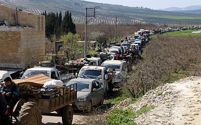 Syrian civilians ride their cars through Ain Dara in Syria's northern Afrin region, as they flee the city of Afrin on March 12, 2018, amid battles between Turkish-backed forces and Kurdish fighters. (AFP PHOTO / STRINGER)