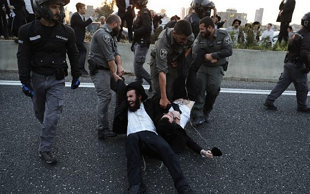 Illustrative: Police remove ultra-Orthodox demonstrators who are blocking a road during a protest against army conscription in the city of Bnei Brak, near Tel Aviv, on March 12, 2018. (AFP Photo/Ahmad Gharabli)