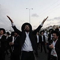Ultra-Orthodox demonstrators block a road during a protest against army conscription in the city of Bnei Brak, near Tel Aviv, on March 12, 2018 (AFP PHOTO / Ahmad GHARABLI)