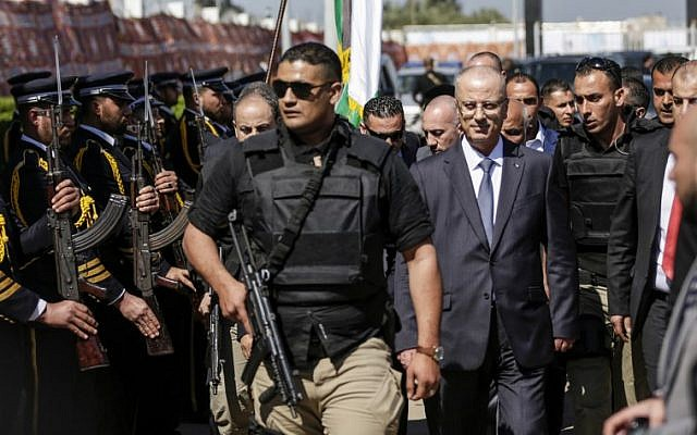 Palestinian Prime Minister Rami Hamdallah (2nd-R), escorted by his bodyguards, is greeted by police forces of the Hamas  terror group (L) upon his arrival in Gaza City on March 13, 2018. (AFP PHOTO / MAHMUD HAMS)
