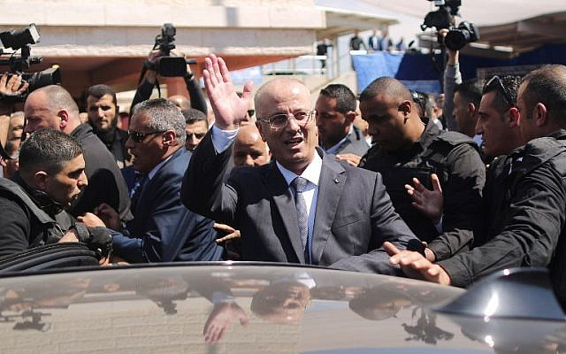 Palestinian Authority Prime Minister Rami Hamdallah waves to the crowd upon his arrival in Gaza City on March 13, 2018. (AFP PHOTO / MAHMUD HAMS)