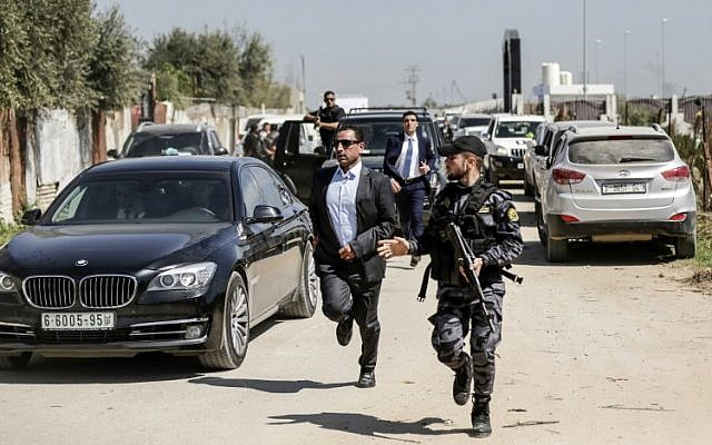 A bodyguard for Palestinian Authority Prime Minister Rami Hamdallah (C) and a Hamasmember (R) escort the PM's convoy as he leaves Gaza City on March 13, 2018. (AFP Photo/Mahmud Hams)