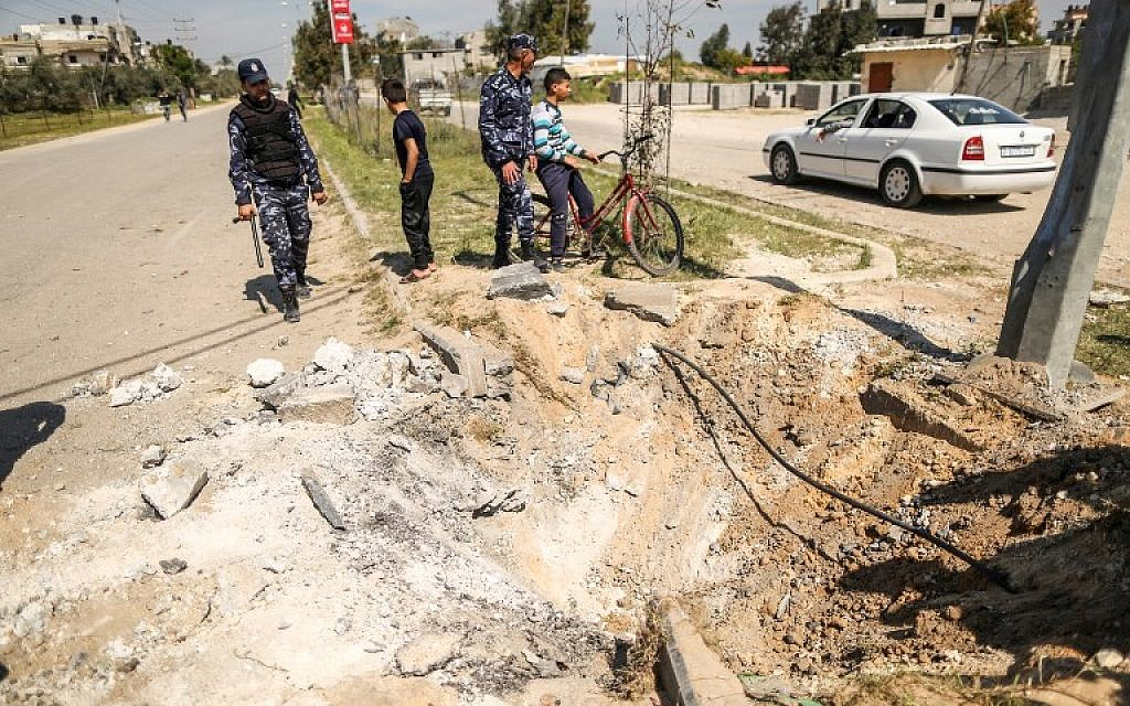 Members of the Hamas security forces inspect the crater left at the site of an explosion that targeted the convoy of the Palestinian Prime Minister during his visit to the Gaza strip on March 13, 2018. (AFP/ MAHMUD HAMS)