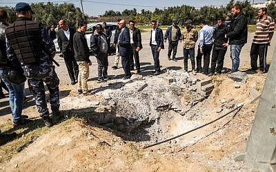 Members of the Hamas security forces inspect the crater left at the site of an explosion that targeted the convoy of the Palestinian Prime Minister during his visit to the Gaza strip, near the Erez crossing, on March 13, 2018. (AFP PHOTO / MAHMUD HAMS)